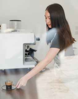 smiling barista serving cup of espresso, witgoed