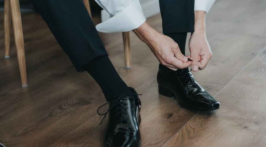 unrecognizable man tying shoelaces sitting on chair