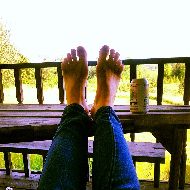 a photo of laurel green's feet on a table with a can of pop beside them