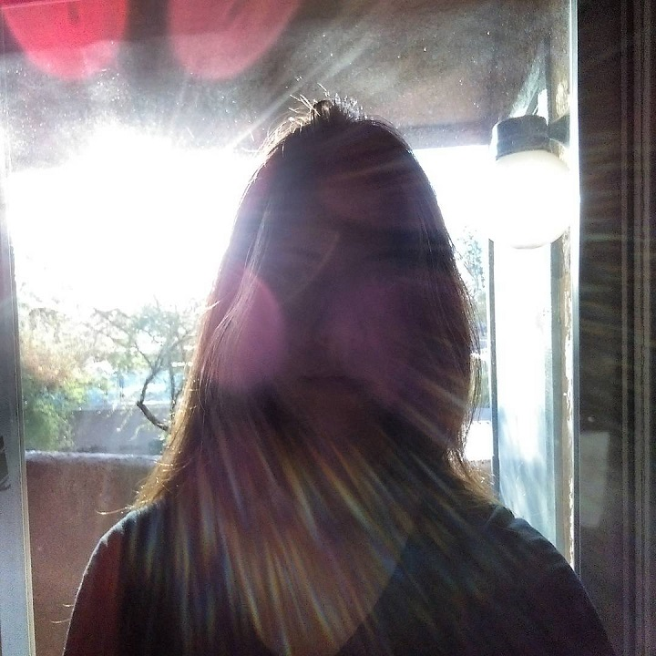 laurel green with sun rays coming from behind and obscuring her