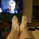 a photo of feet wearing moisturizing booties in front of a tv