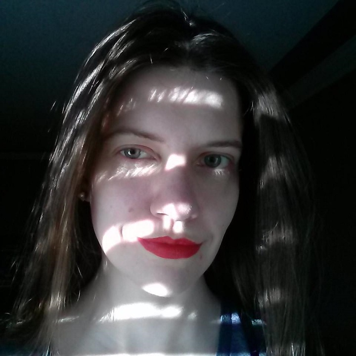 photo of laurel green wearing red lipstick with her face partially shadowed