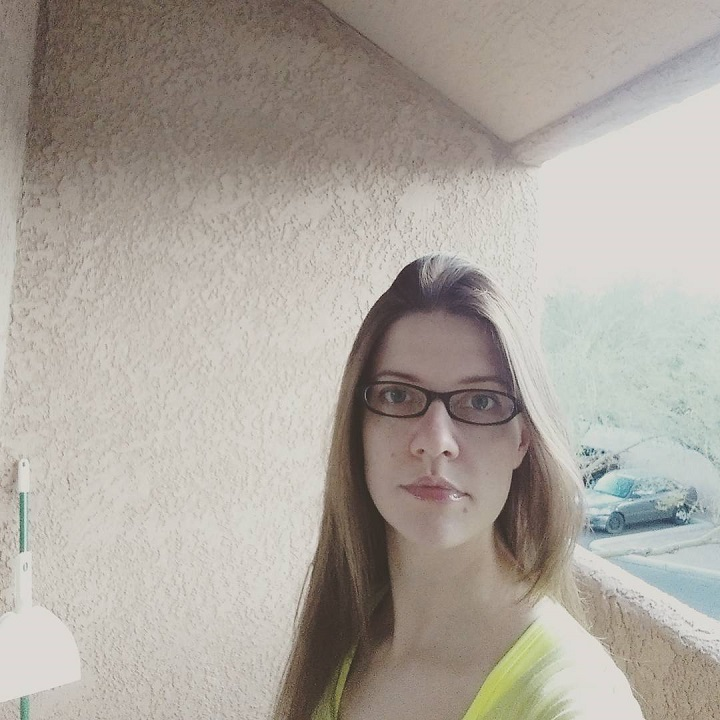 laurel green wearing a yellow shirt and glasses on a balcony