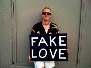"guy holding ""fake love"" sign"