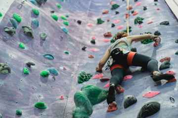 female sportsman training climbing on rock climbing wall at gym