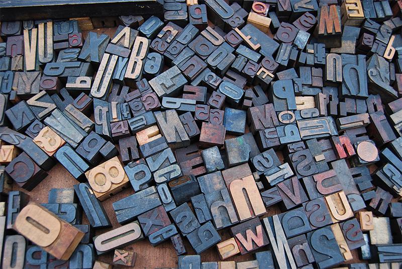 Des lettres d'imprimerie sont disposées en tas symbolisant la liste des différentes structures de la figure de style d'analogie