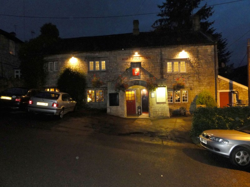 Nightime photo of the front of the Hop Pole Inn, built on a hillside, with cars parked in front