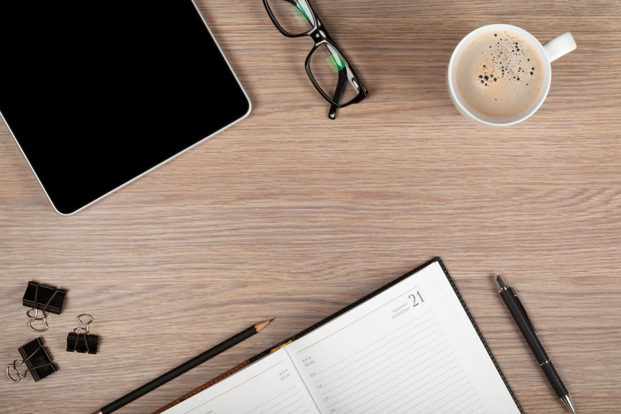 22271434 - tablet, notepad, glasses and coffee cup on office wooden table