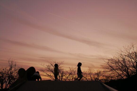 夕暮れ時に遊ぶ子供