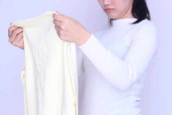 伸びたtシャツを見る女性