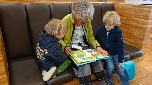 絵本を見る子供2人とおばあちゃん