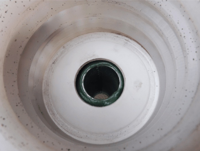 This is the interior of the cap for the fuel jug. The standard fill hose was too restrictive for a car we were racing with a fuel cell so we drilled out the stock mount for the fill hose and replaced it with a larger piece of tubing. You can see here the tubing is thin walled to help with flow and it is held in place with the green 3M epoxy.