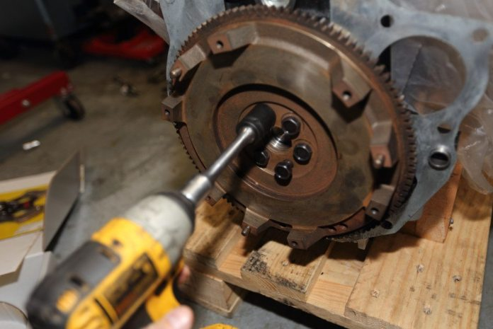 Start the flywheel bolts by hand, then run them in with an impact gun. No need to hammer them in with the impact. You're going to tighten them using a torque wrench.