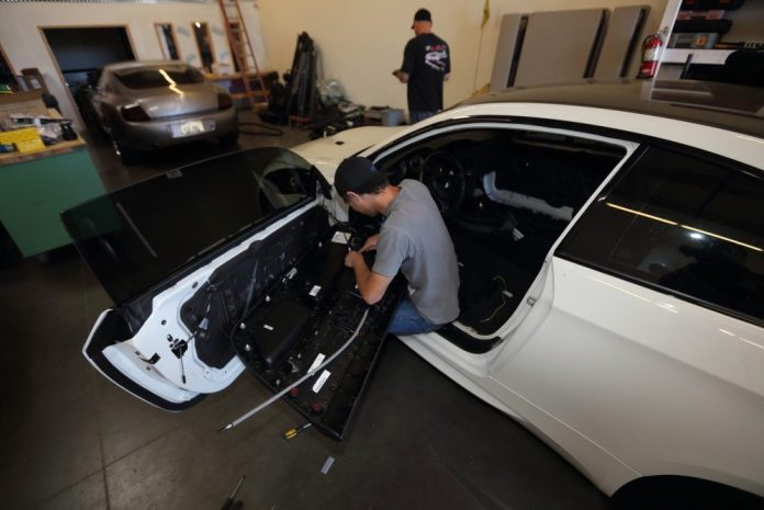 Ben Wilkinson removes the interior door panel in preparation for removing the window glass and cutting the inner door panel to accommodate the roll cage.
