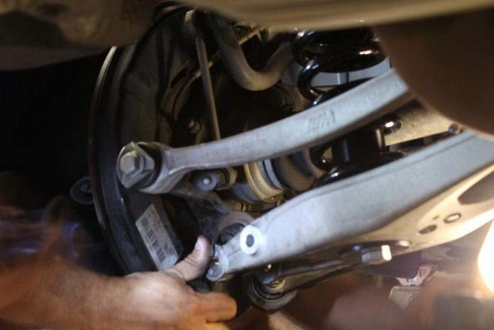 ITDG's Patrick Orozco begins disassembling the rear suspension to install the D2 triple-adjustable shocks and springs.