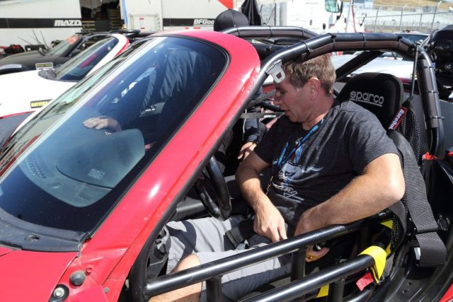 PTB and TTC Champion Dave Schotz works with a Skip Barber technician to get fitted into his car.
