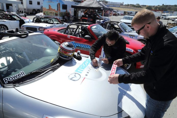 NASA Florida driver Chi Ho helps fellow Orlandoan Eric Powell apply decals to Powell's car Wednesday afternoon.