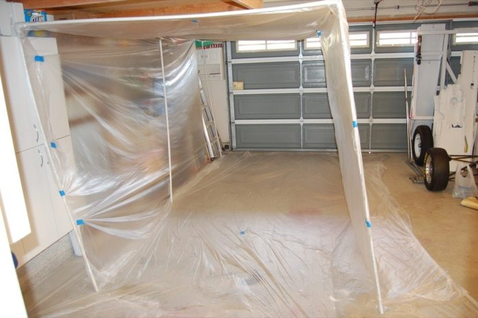 If you have a garage bay that you need to convert to a paint booth, all you need is a big roll of wide, clear plastic sheet from your local paint supply store, several lengths of PVC plastic pipe, and several three- and four-way elbow fittings for them. Three-quarter-inch PVC pipe is the smallest size that will make a self-supporting frame. Half-inch can just barely be made to work by leaning the frame against a wall. Start by taping a sheet of plastic on the floor, then dry assemble the PVC frame without any adhesive. Drape plastic sheet over the top and all sides of the frame, and you have created a non-ventilated paint booth. Use a good painting respirator and take a breathing break every few minutes.
