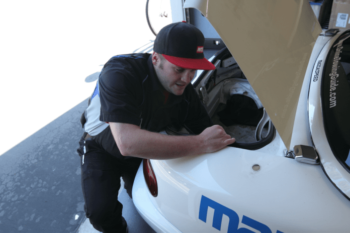 Morgan Jerbiss of Sampson Racing Communications sands the paint off the inside of the quarter panel to get good contact for the remote antenna, which must be mounted to metal.
