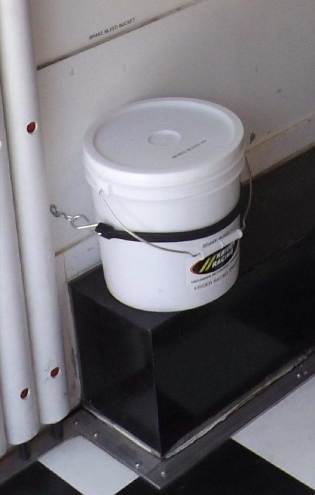 The brake bleed bucket is easy to store in a racing trailer. Here we used two eye bolts and a rubber strap to hold it in place. The best part is no matter how much the trailer jostles around, all of the greasy brake bleed tools are safe in the bucket keeping the harmful brake fluid far from our race car's shiny paint job.