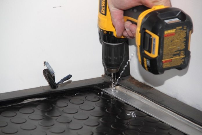 Drill pilot holes through the strip, mat and floor. Then drill holes in the strips that will accommodate the diameter of the screws.
