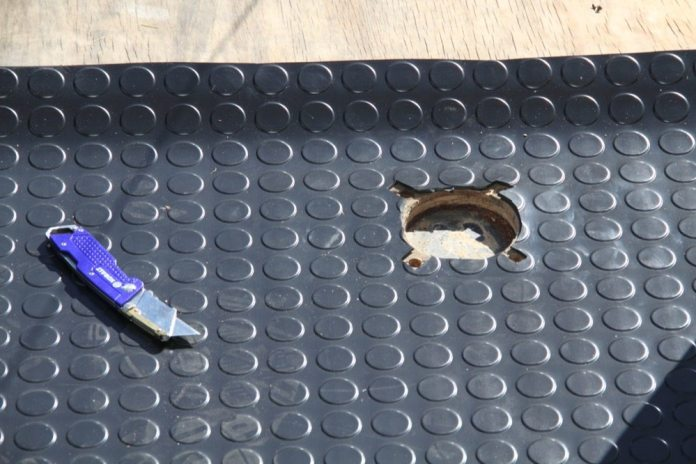 The holes for the D rings are easy to find. Just cut the mat away to accommodate the recessed cup and the bolt holes.