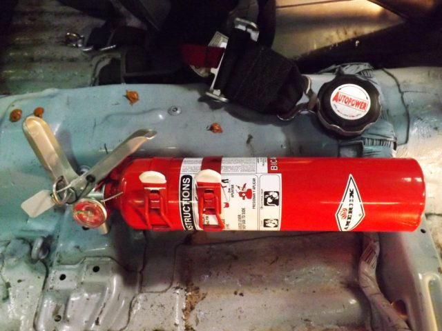 The trick to installing a fire extinguisher in a NASA racecar is the requirement that a driver can access it while strapped in the seat. Fire extinguishers are heavy. We installed ours as low as possible to keep the weight down in the car. We use the double-strap extinguisher mount from I/O Port Racing Supplies to ensure the heavy extinguisher doesn't come loose and end up underneath our brake pedal.