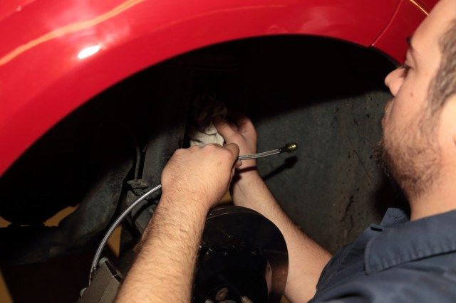 Bushman routes the braided stainless-steel brake hose to the hard line on the chassis.