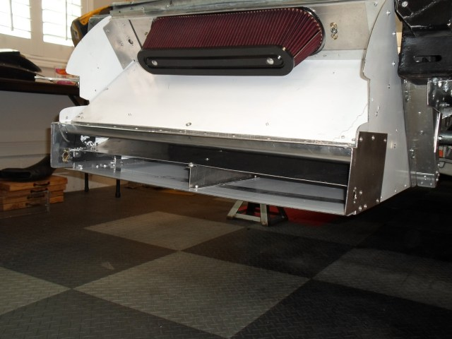 Air for the radiator goes between the bumper fascia and the splitter. Air for the engine is gathered by vents on both sides of the fascia.
