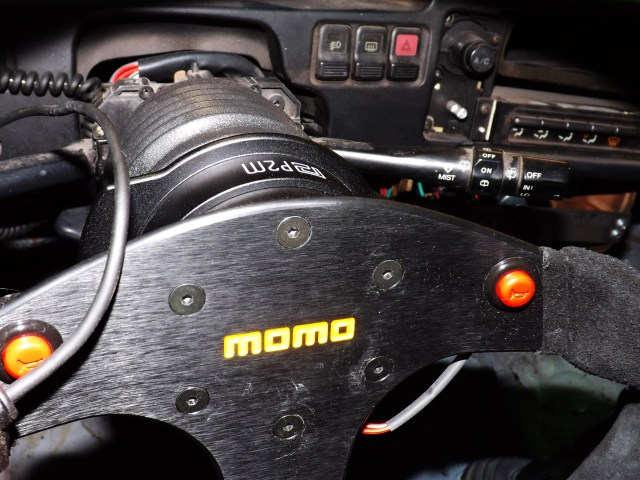 You can see the little wings of the Phase 2 Motortrend steering wheel quick release behind our Momo wheel. This design makes the piece easy to use by extending your fingers from the wheel to pull back on the quick release to get the wheel out of the way rapidly.