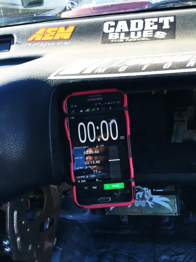 Using some zip ties and a cheap phone case, we used some existing holes where the glove box used to be and tied the case to the dashboard. We picked a spot where I could see the lap times as I crossed start/finish.