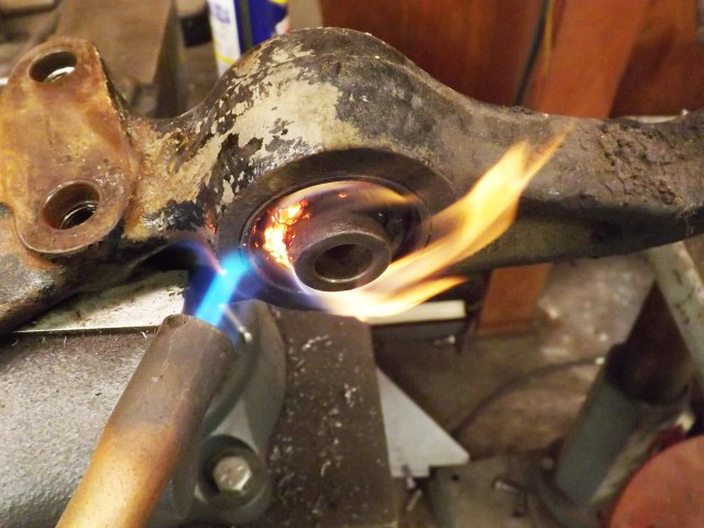 The easiest way to get this pesky rubber bushing out of the lower control arm is to burn it. A small bottle torch and a lighter will get you on your way.