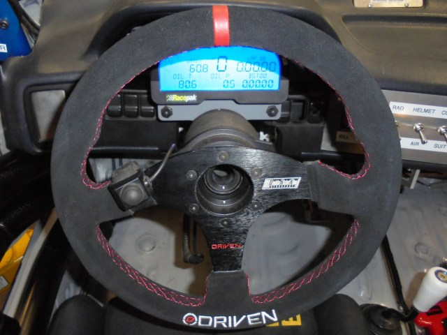 To get the car to go through the corners, we installed a custom Driven steering wheel with our Double Nickel Nine Motorsports logo on it, and added a push-to-talk button from Sampson Racing Communications.