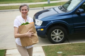 woman carrying meal in a shopping bag to doorstep