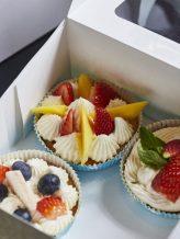 Die fertigen Muffins mit einer Creme und hübsch dekoriertem Obst darauf.