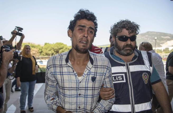 "A Turkish police officer escorted suspect Hassan Ali Salih to court in Bodrum. He was charged with ""conscious negligence"" for allegedly organizing the trip that killed Syrian toddler Aylan al-Kurdi. (Courtesy of eshopmall.co.uk/Roland Hoskins)"