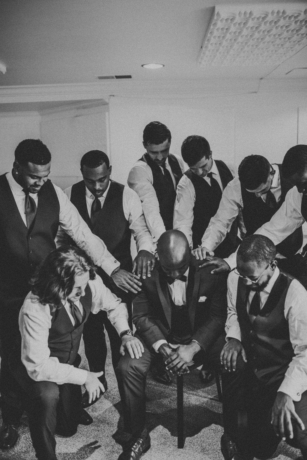 groom with groomsman praying