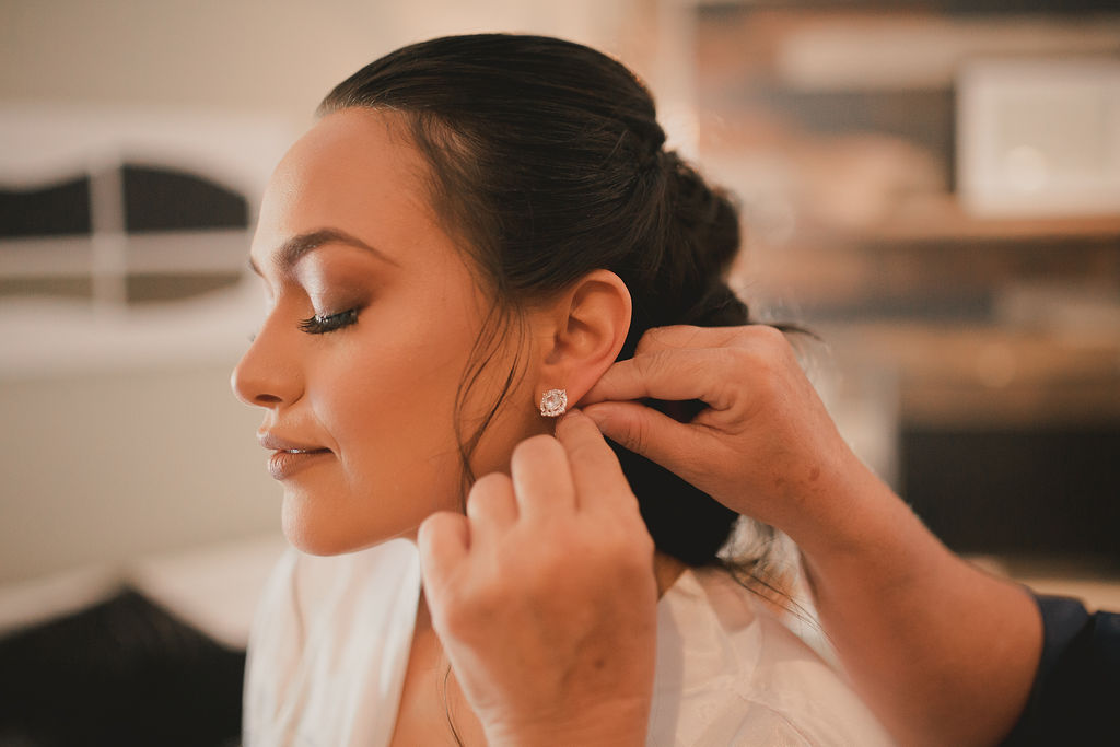 Bride putting on wedding earrings