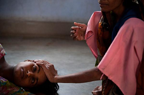 ROTHAK, ROTHAK, INDIA – NOVIEMBRE 2, 2009: Una mujer cuida a Namita (18 años) en una casa protegida en Rothak. Namita fue tomada desde su hogar en West Bengal para ser vendida como esposa en Haryana. Está embarazada tras ser violada por su traficante y sufre problemas mentales. El hogar les otorga protección física pero también ofrece otros recursos a mujeres que han sido traumatizadas física, mental, emocional y sociológicamente. Walter Astrada/Alexia Foundation