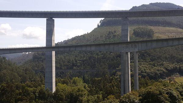 En un valle se cruzan dos puentes por los que transitan coches. Hay dos alturas. Al fondo se observa el antiguo puente con ojos que atravesaba el valle sembrado de árboles.