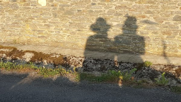 Sombra de dos peregrinos sentados reflejadas en el camino y un muro de piedra al atardecer
