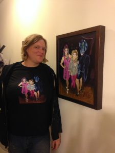 """The artist wearing her """"Three Fancy Ladies"""" t-shirt in front of the original oil painting: three """"Three Fancy Ladies"""""""