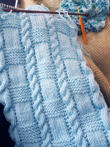 Photograph of the Assembly scarf in progress on knitting needles