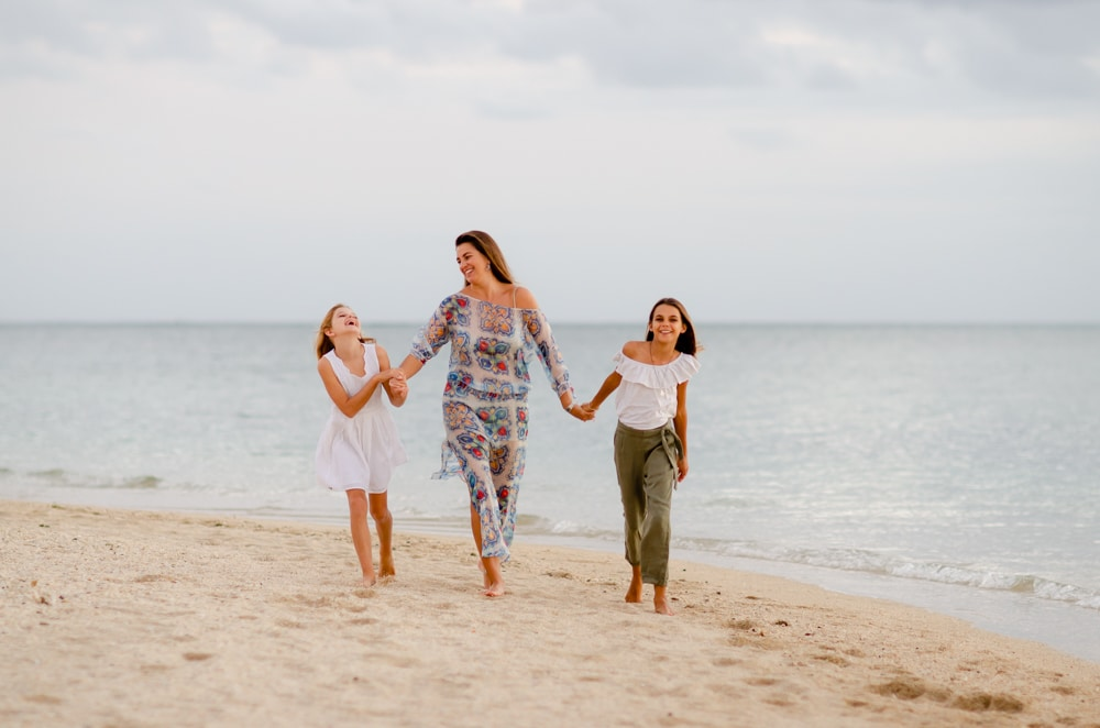 mother stylishly dressed strolling on the beach with her daughters
