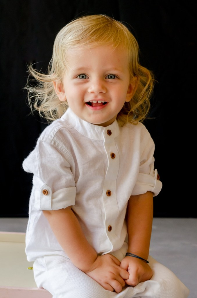 Toddler in white outfit smiles for the camera for his school photo day