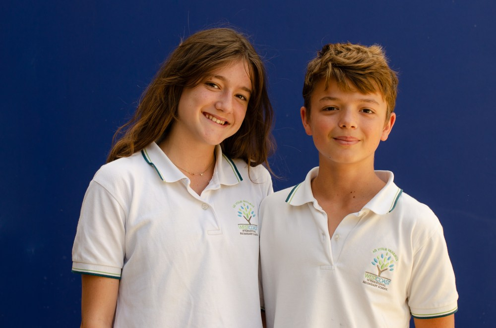 brother and sister  pose for a school photo in their school uniforms