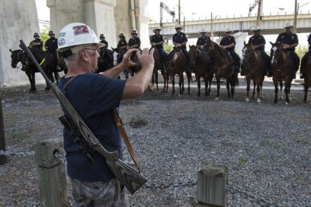 CLEVELAND, OH - JULY 18: Elam Stoltzfus of Lancaster, Pa., carrying his hunting rifle, photographs a phalanx of mounted police officers near a pro-Trump rally in Cleveland on July 18, 2016. (Photo by Michael Robinson Chavez/The Washington Post via Getty Images)
