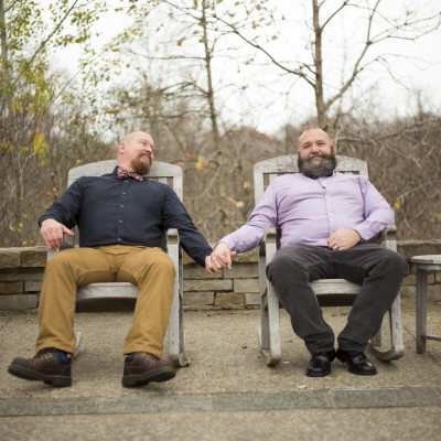 Two men holding hands sitting in Adirondack style chairs - michigan gay engagement photographer
