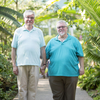same sex engagement session of two men holding hands and walking through a garden - Michigan wedding photographer