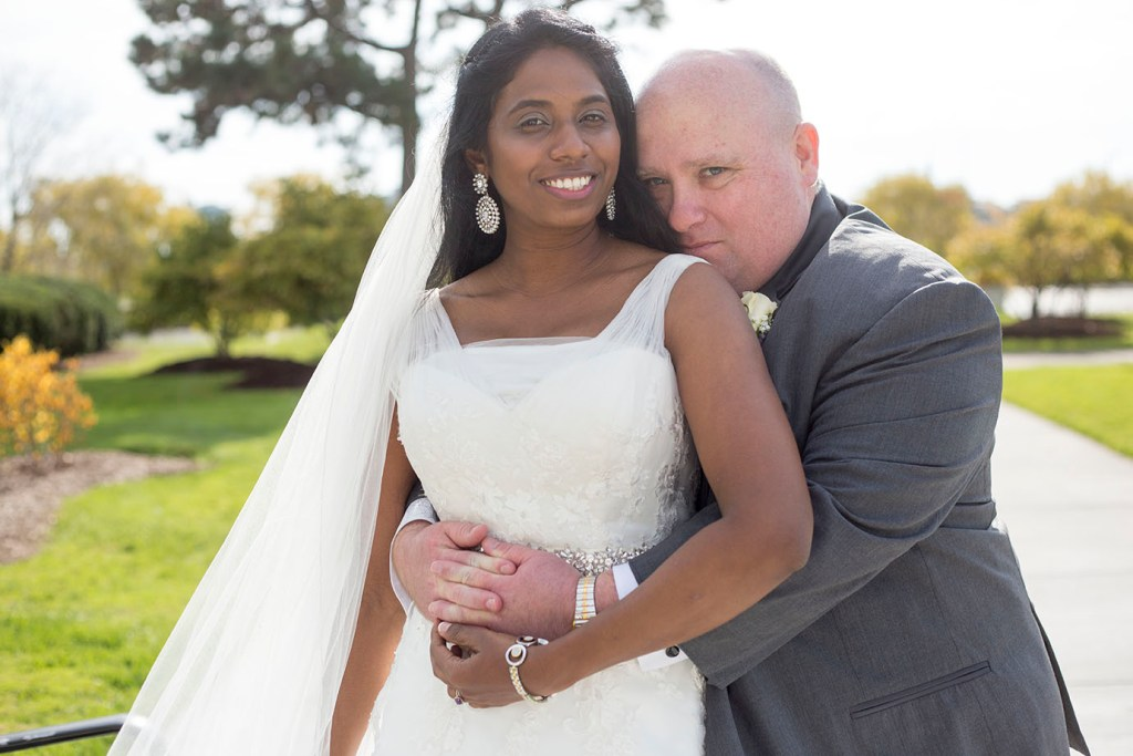 Couple cuddles after their Belle Isle wedding in Detroit